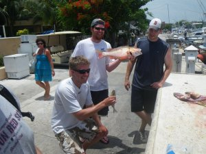Displaying part of our catch: Grant, my brother in law on the left, Jon, my best man, in the center, and myself next to a pile of discarded fish parts