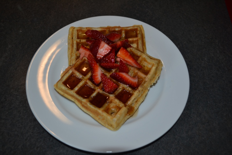 Whole wheat waffles with bourbon syrup and sliced strawberries