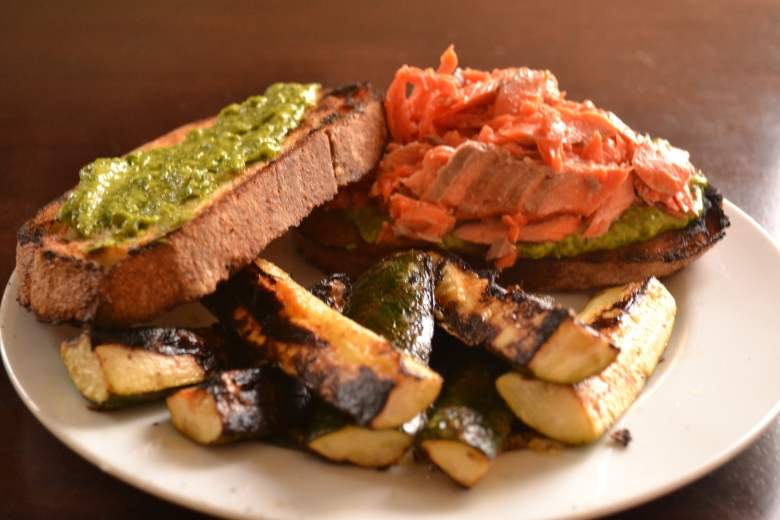 Flaked salmon sandwich with avocado pesto some grilled lemony zucchini